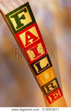 STACK OF WOODEN TOY BUILDING BLOCKS SPELLING THE WORD FAILURE
