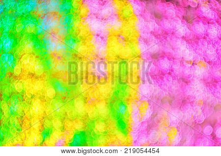 Defocused background light blurred bokeh of festive paper with glitter in soft focus multi colored vibrant image with refraction copy space
