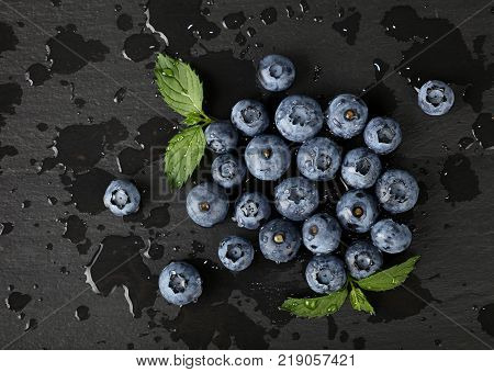 Close up fresh washed blueberry berries with water drops and green mint leaves on black slate board elevated top view directly above