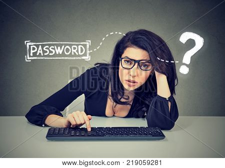 Upset woman typing on the keyboard trying to log into her computer forgot password
