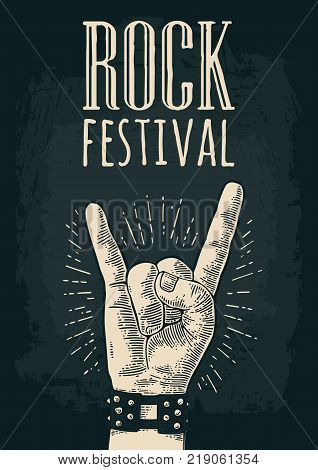 Rock and Roll sign. Hand with metal spiked bracelet giving the devil horns gesture. Vector monochrome vintage engraved illustration. Isolated on dark background. For festival poster