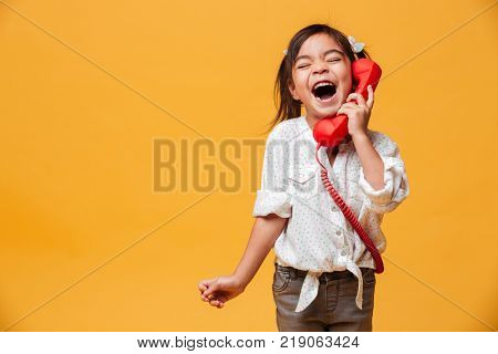 Image of screaming excited little girl child standing isolated over yellow background talking by red retro telephone.