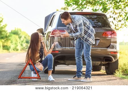 Young couple quarreling near broken car on road