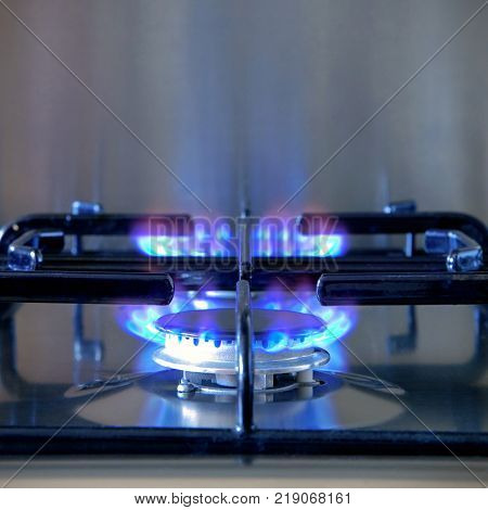 Two gas rings alight on a modern brushed steel hob.