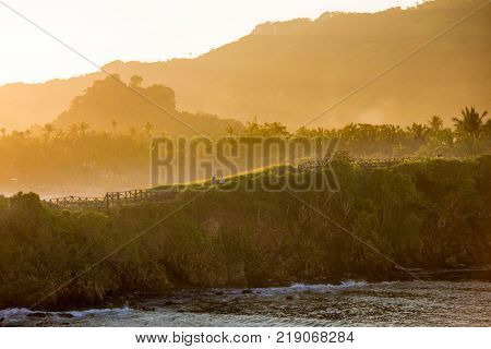 Tourists walk an oceanside path at dawn in the Dominican Republic