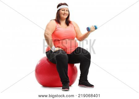 Overweight woman sitting on an exercise ball and exercising with a small dumbbell isolated on white background