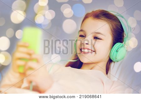 people, children and technology concept - happy smiling girl lying awake with smartphone and headphones in bed listening to music at home over holidays lights