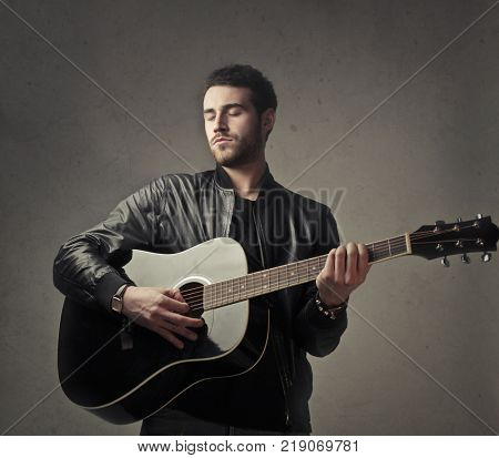 Handsome young man playing guitar