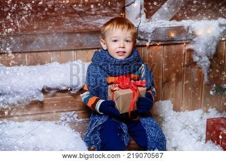 Adorable child boy in winter clothes sits on the porch of the magic house of Santa Claus with gift box. Miracle time. Merry Christmas and Happy New Year.