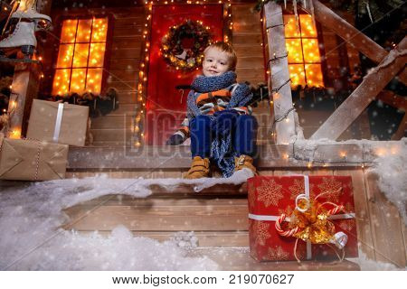 Cute little boy in winter clothes sits on the porch of the magic house of Santa Claus with gift box. Miracle time. Merry Christmas and Happy New Year.
