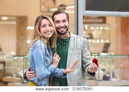 Man and his beloved girlfriend with ring near jewelry store