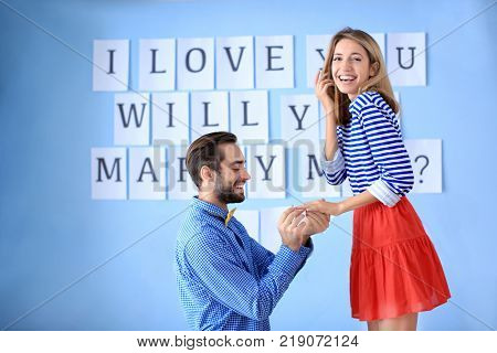 Young man offering hand to his beloved girlfriend against wall with marriage proposal on engagement day