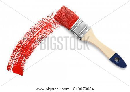 Brush and red paint stroke on white background, top view