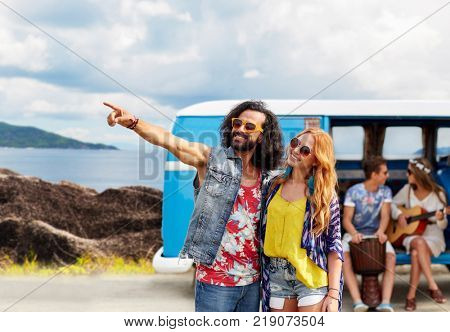 summer holidays, road trip, travel and people concept - smiling young hippie couple with friends in minivan car over island and sea background