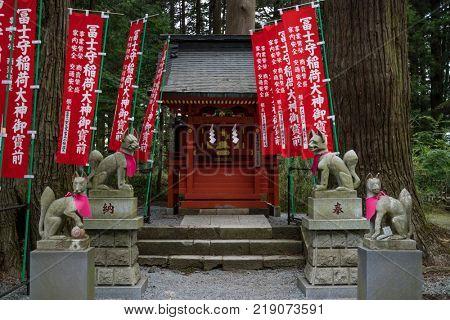 Fujiyoshida city - Japan, June 13, 2017; Votive Kitsunes, fox figurines, animal guardians in front of an Inari Shrine with red shrine banners