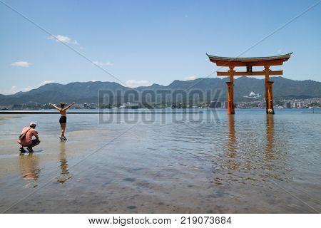Miyajima - Japan, May 26, 2017: Red Torii gate of the Itsukushima Shrine in the sea at low tide with tourists near Miyajima