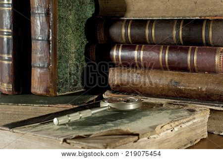An ancient book in a ragged cover and a magnifying glass on a table closeup on a blurred background of other old books