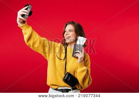 Portrait of a smiling woman taking a selfie while holding passport with flying tickets isolated over pink background