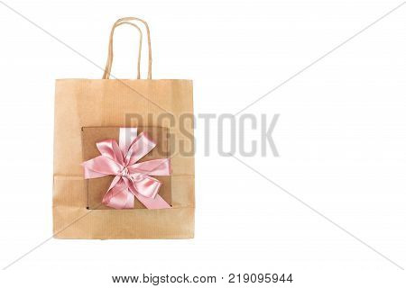 Paper bag for shopping and gift box tied with a satin pink ribbon. White background isolated