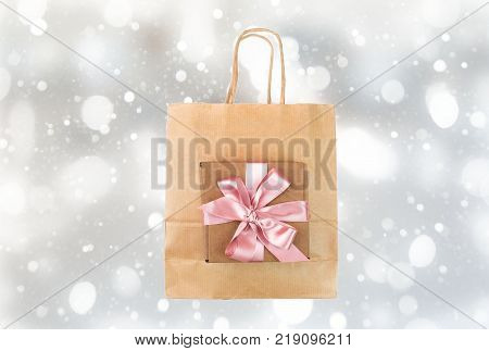 Paper shopping bag and gift box, tied with satin pink ribbon. Texture festive background gray