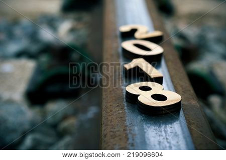 closeup of four wooden numbers forming the number 2018, as the new year, on a rail of a railway, metaphor of the beginning of a new year as a journey