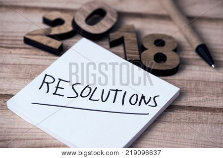 four wooden numbers forming the number 2018, as the new year, a note with the text resolutions and a pen, on a rustic wooden table