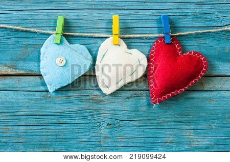 Valentine background with sewed pillow diy handmade hearts on clothespins at rustic wood planks.