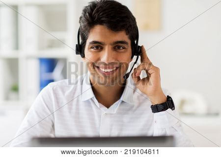 communication, business, people and technology concept - businessman or helpline operator with headset and laptop computer at office