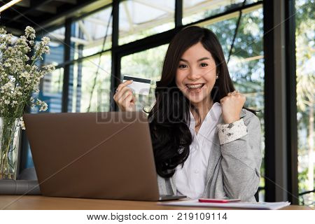 young happy woman holding a credit card and using laptop computer for online shopping at cafe. businesswoman purchase goods from internet at office. female adult raise fist with yes gesture