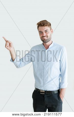 Closeup portrait of smiling handsome young man pointing finger aside. Young manager recommending product or service or  making business presentation. Business promotion concept