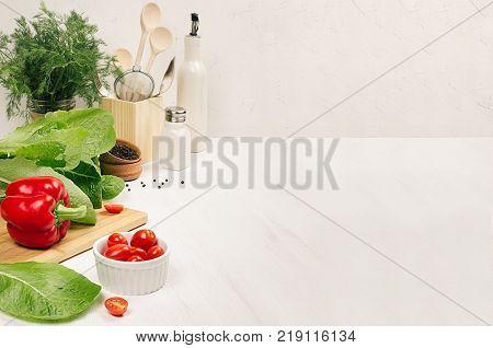 Healthy vegetarian ingredients for spring fresh green salad and kitchenware in white elegant kitchen interior. Spring vitamin dieting food.