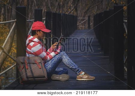 Beautiful woman of a student sitting at the bridge with reading tablet and relaxing on a park background. Education concept. Copy space.