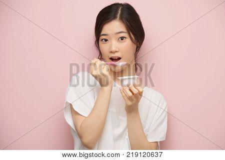 Portrait of Korean young woman eating tasty yogurt