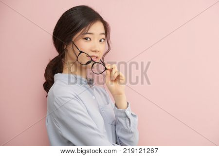 Pretty Korean young woman with glasses standing against light pink background