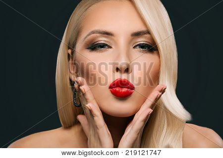 beautiful glamorous woman with makeup and hairstyle blowing kiss, isolated on grey