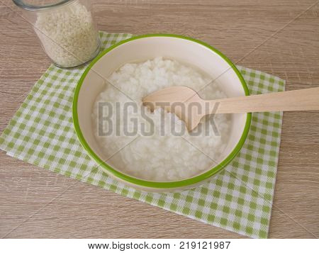 Congee with rice in bowl and glass of rice