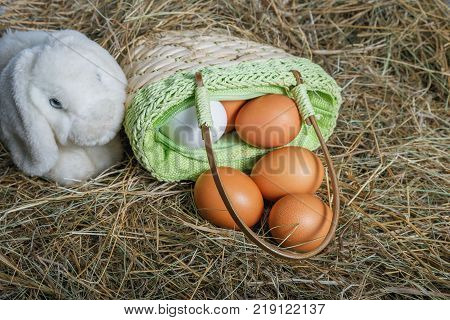 Easter composition. A few eggs in the straw bag and the toy rabbit closeup