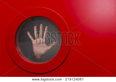 Round red porthole with female hand. Сopy space