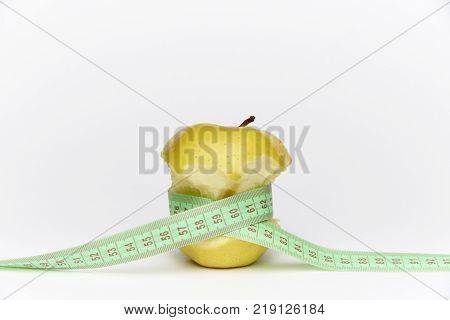 Yellow ripe bitten apple with a meter on a white background