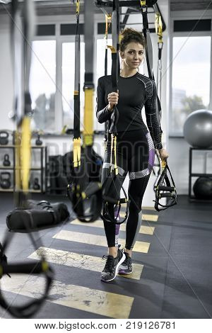 Delightful girl is posing between hanging TRX straps in the gym on the windows background. She wears a dark sportswear with sneakers. Woman holds the straps and looks into the camera with a smile.