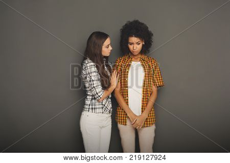 Woman hugging her depressed friend, gray studio background. Young girl supporting her crying girlfriend. Friendship consoling and care, copy space