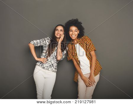 Girl overhearing her girlfriend mobile phone talk, gray studio background. Young women having fun, making group conversation, copy space