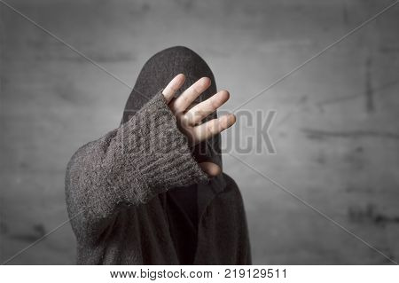 Celebrity is hiding face with a hand from paparazzi photographers. Stop gesture no photo.