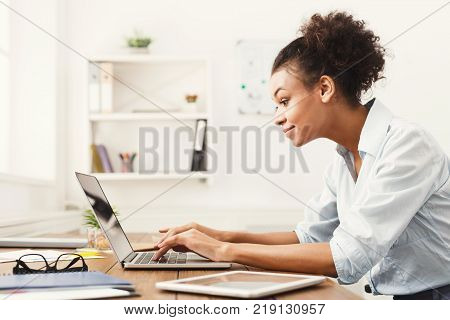 Happy african-american business woman working on laptop at office. Businesswoman typing something on computer while sitting at her working place, copy space