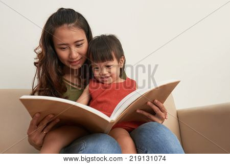 Mother reading book to her little daughter