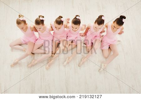 Little girls dancing ballet in studio. Young ballerinas stretching before performance, classical dance school, copy space, top view