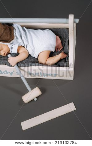 partial view of adorable baby with hammer in hand sleeping in wooden toolbox with daddys helper lettering