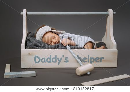 adorable baby with hammer in hand sleeping in wooden toolbox with daddys helper lettering poster