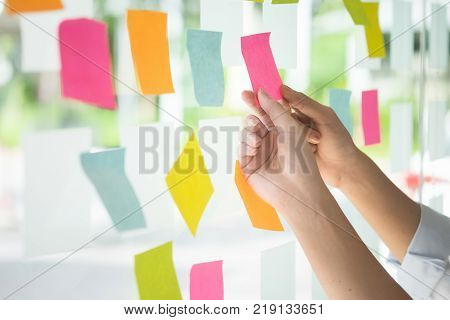 Creative business people reading sticky notes on glass wall with colleague working use post it notes to share idea discussing and teamwork brainstorming concept.Closeup shot.