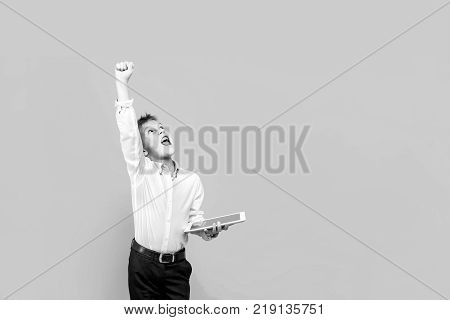 Happy young boy in formal clothing using tablet. Studio shot isolated on yellow. Winner.
